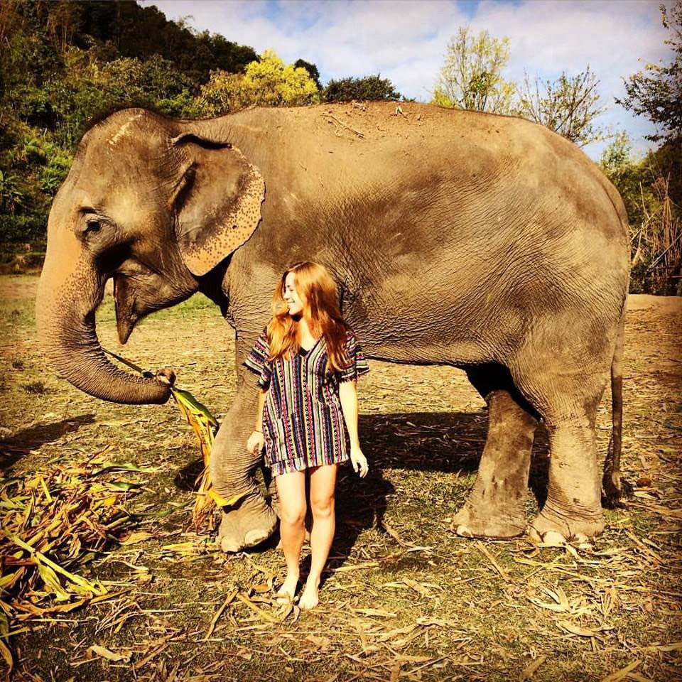 A girl standing barefoot with an elephant