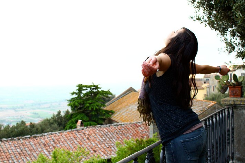 woman stands at railing overlooking Tuscan view of rooftops and fields in the distance with her eyes closed, face to the sky, and arms wide open