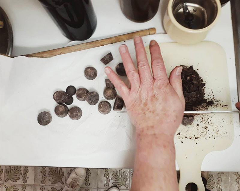 grandmother's hand chopping dark chocolate for gelato