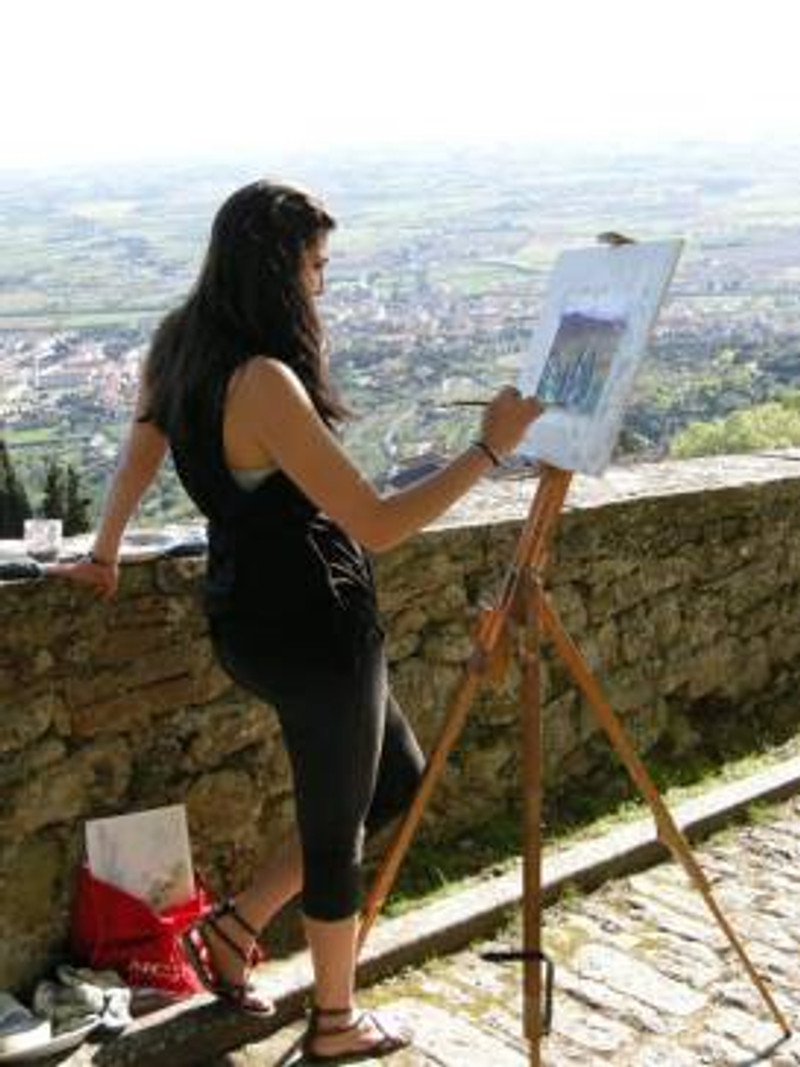 artist painting in cortona, italy with view over tuscany