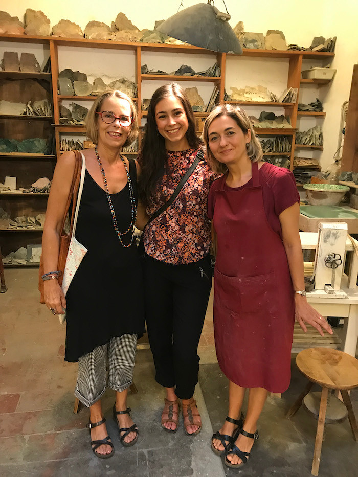 three ladies in an artisan workshop in Florence with shelves of stone materials behind them