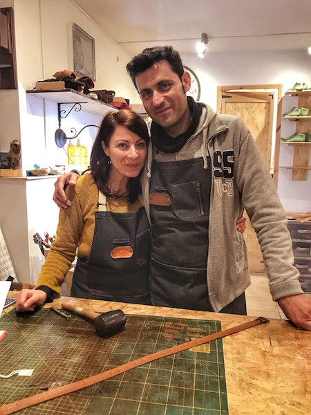 Italian couple wearing aprons and standing in their artisan leather workshop