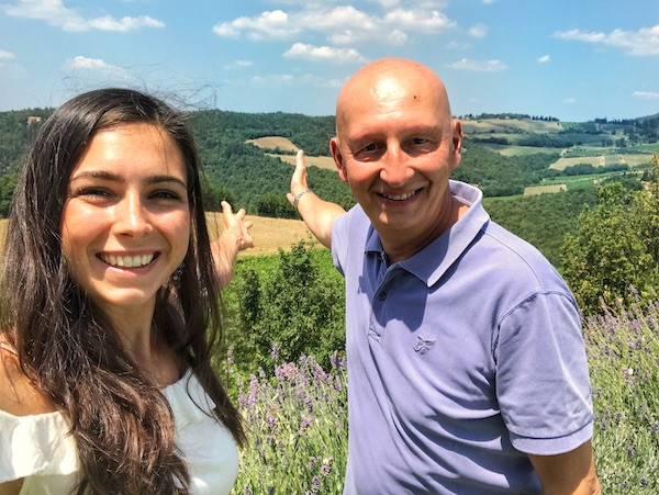 young woman and older bald man gesturing to the beautiful Tuscan view and smiling in the sun