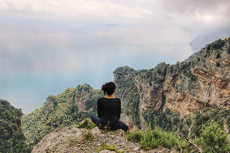 woman sitting on a cliff ledge overlooking the mountains along the Amalfi Coast and out to sea