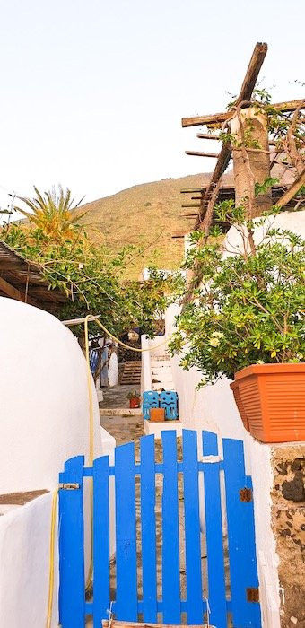 a bright blue gate in front of a traditional home on the island of Stromboli