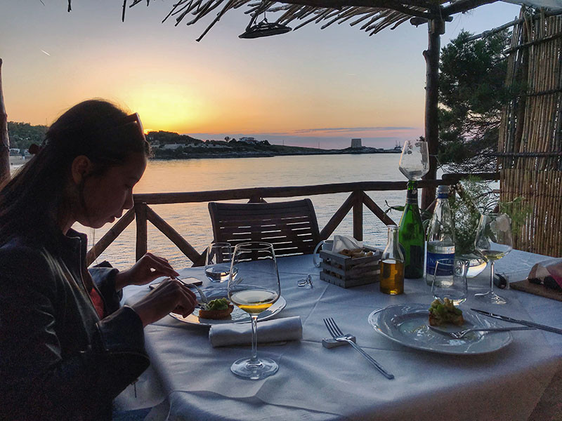 the silhouette of a woman eating at a fine dining table with the sunset behind