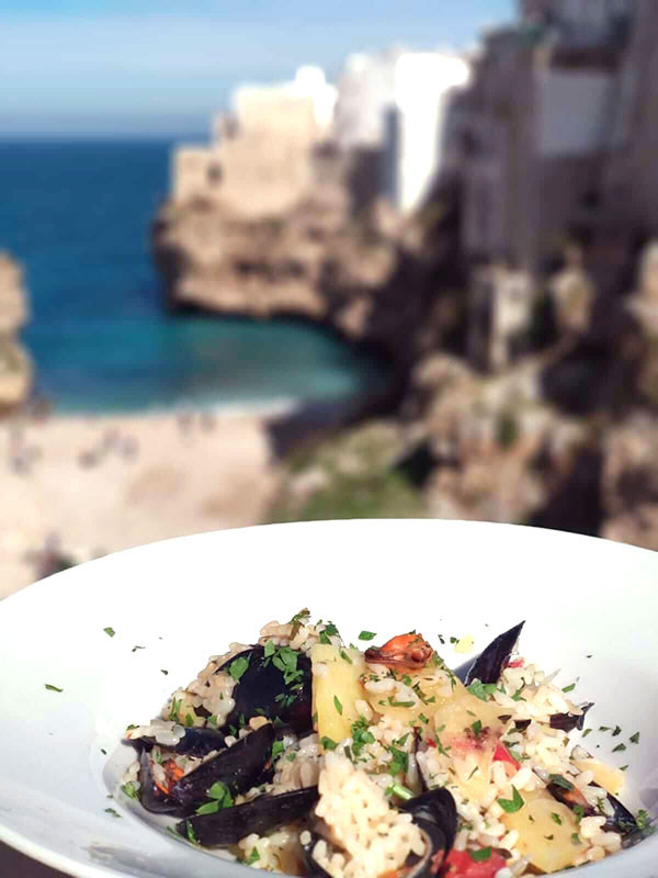 plate of rice potatoes and mussels in with a background of Polignano a Mare seaside cliffs