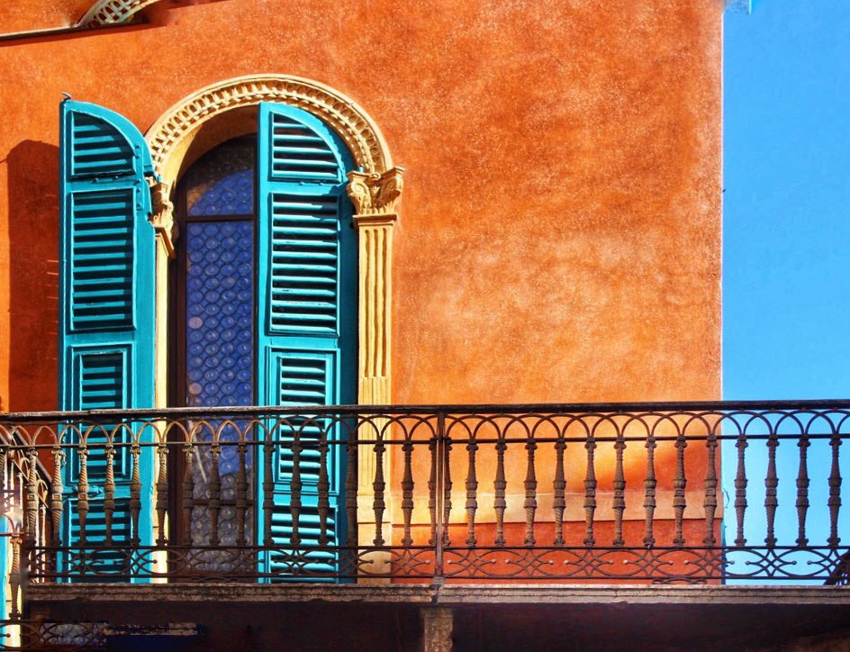red-building-with-arched-window-and-teal-shutters-in-verona-italy