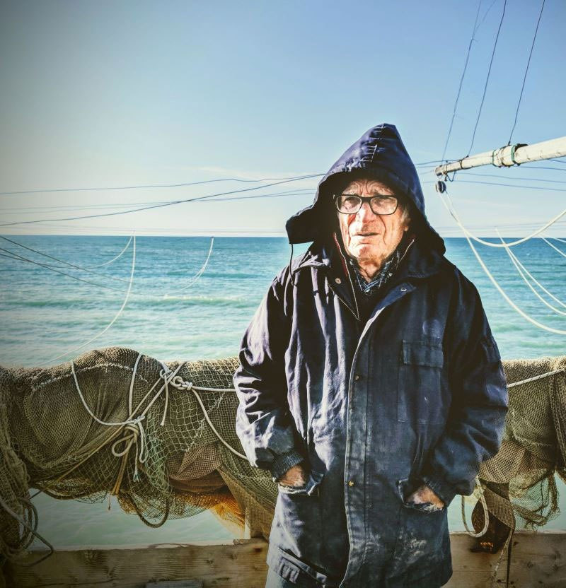 An older Italian man in a weathered blue hooded coat, stands with his back turned on fishing nets handing on a wooden boat, against the light blue sea.