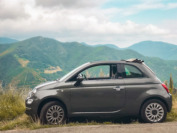 grey convertible fiat car parked in front of a mountain view