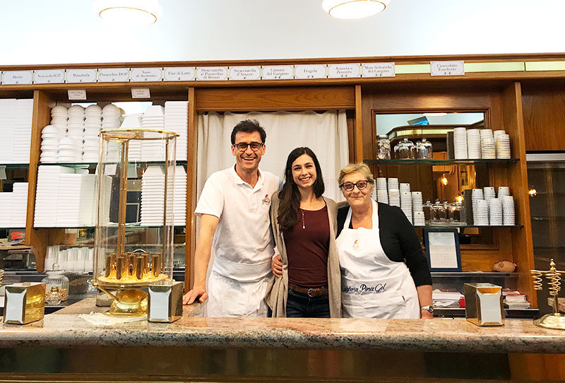 A dark-haired woman smiling and posing between Italian gelato makers behind their gelato counter