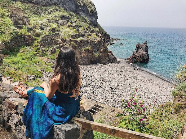 lady wearing a blue dress looking over a view of a rocky beach in the aeolian islands