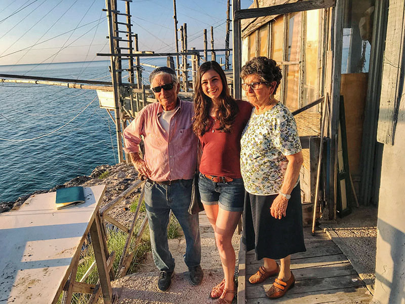 brunette woman posing with an elderly couple in front of a trabucco on the sea in gargano italy