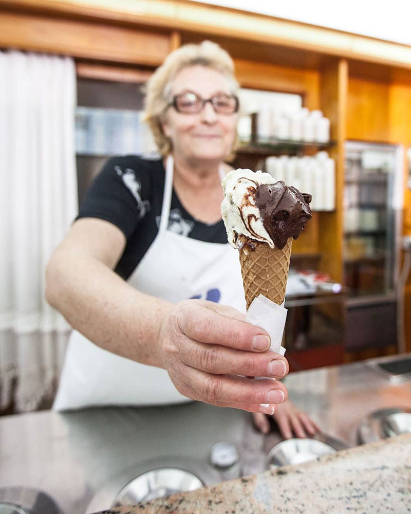 Chocolate and stracciatella ice cream cone held out towards the camera by an older woman gelato maker