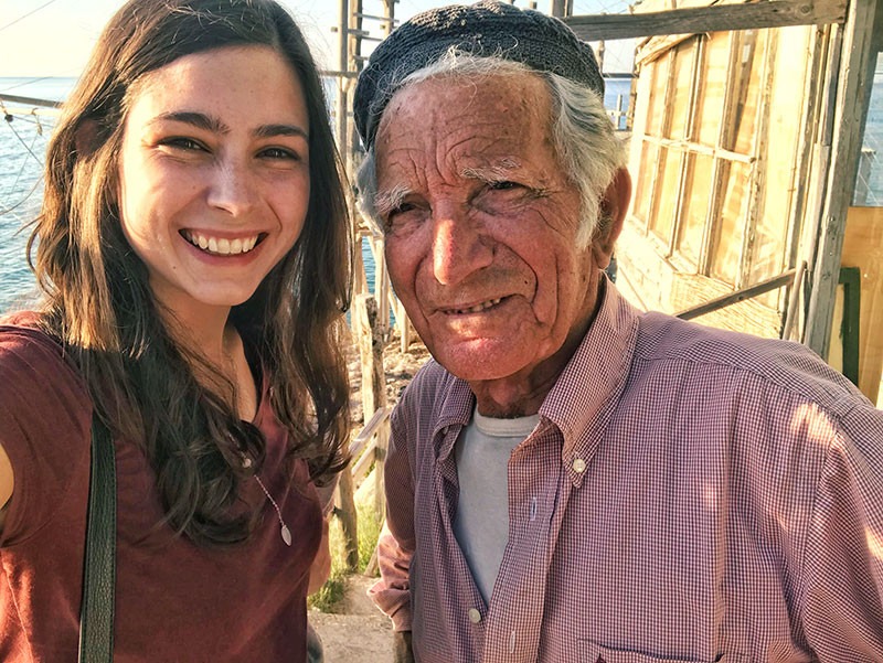 young woman taking a selfie with an old fisherman on his trabucco in Gargano Italy