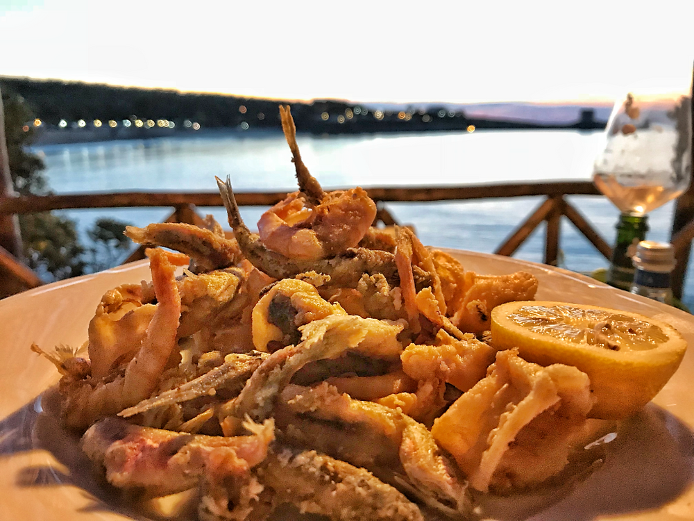 A white plate of fried calamari and shrimp with a fresh lemon on the side. With the twinkling lights of a coastal city reflecting off the ocean at twilight.