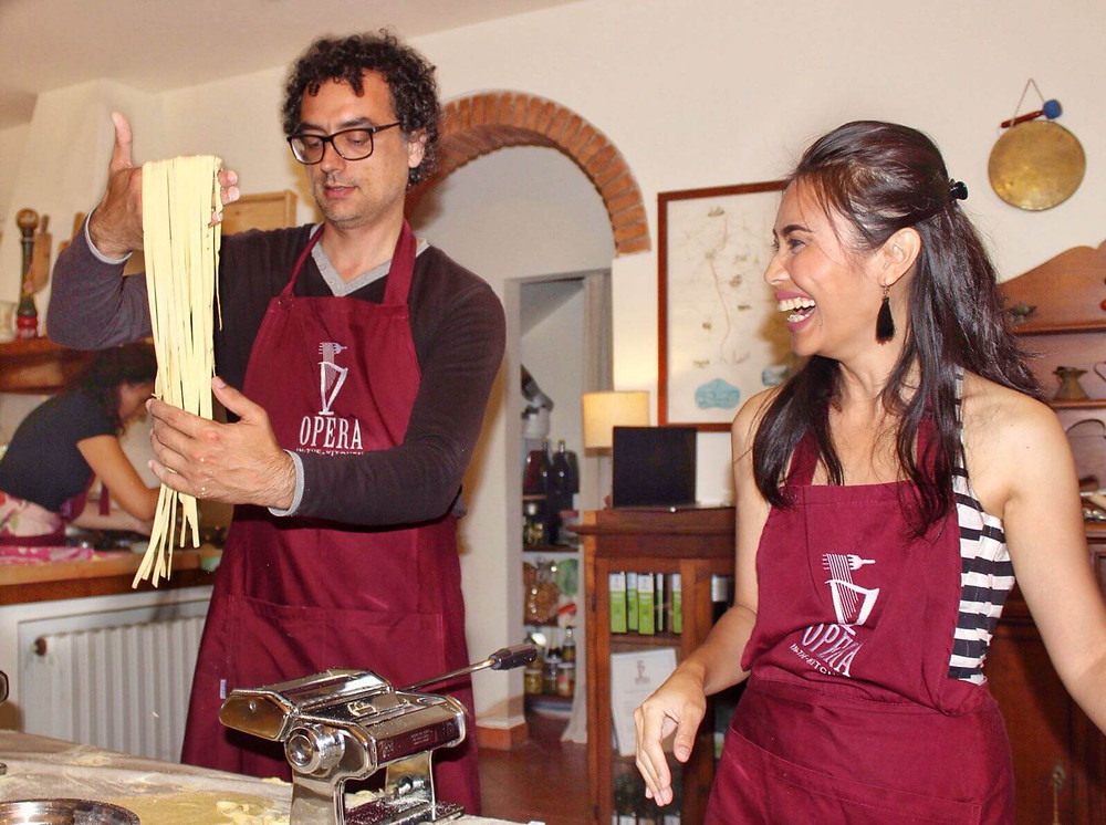 man making fresh pasta with girl laughing