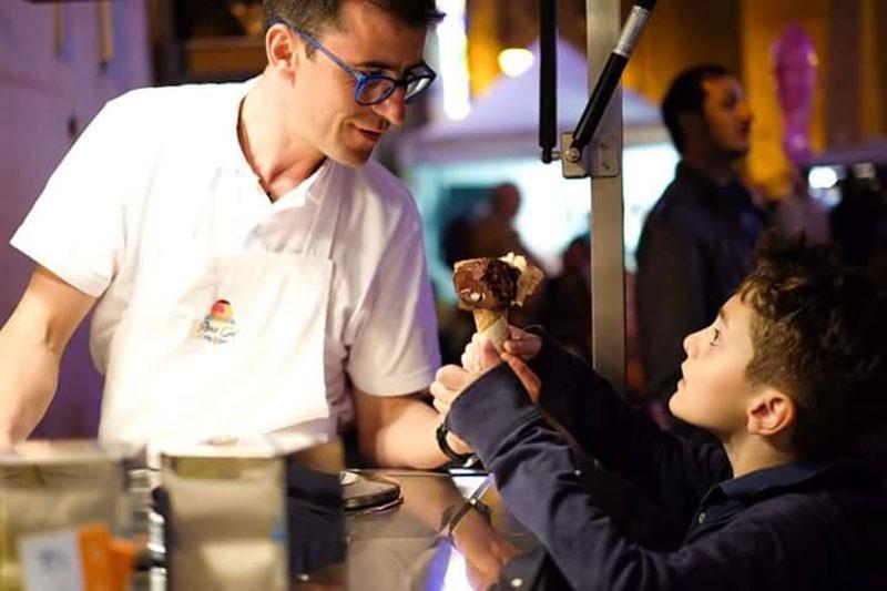 an italian man serving gelato to a little boy at night
