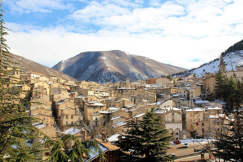 stone village in Italy with snowy rooftops and mountains