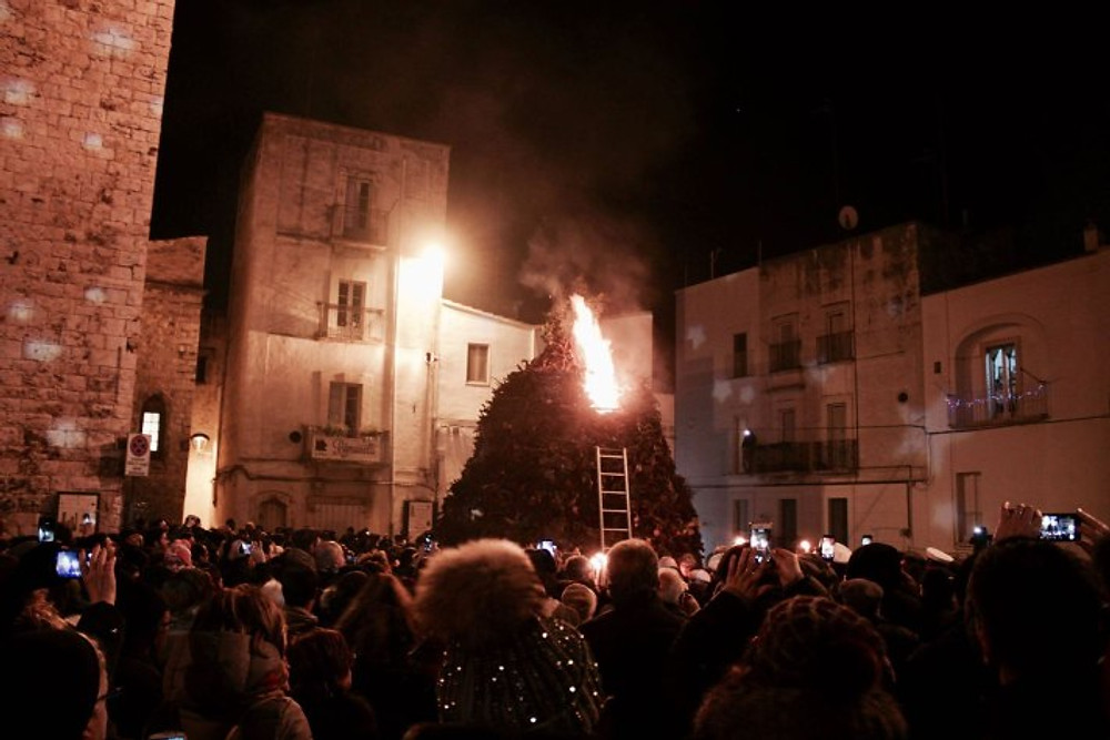 in a stone village in italy at night, a crowd stands around a huge pile of sticks and logs. a ladder is leaned up against this bonfire and someone at the top is lighting it