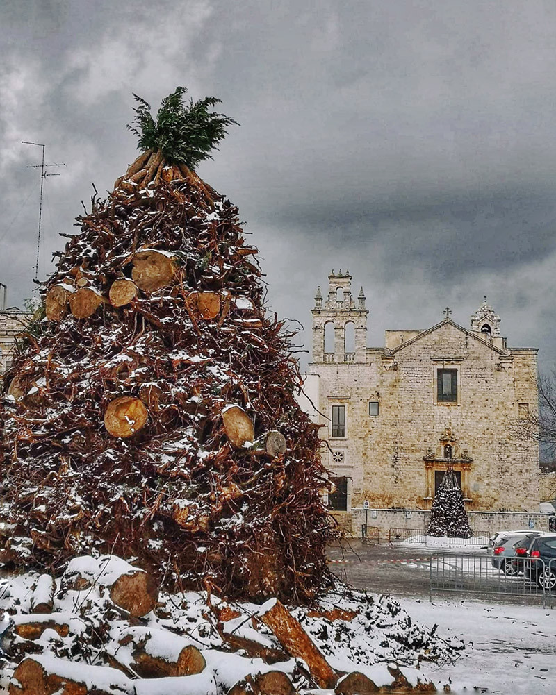 an enormous pile of sticks and logs dusted with snow in an italian piazza with cloudy skies