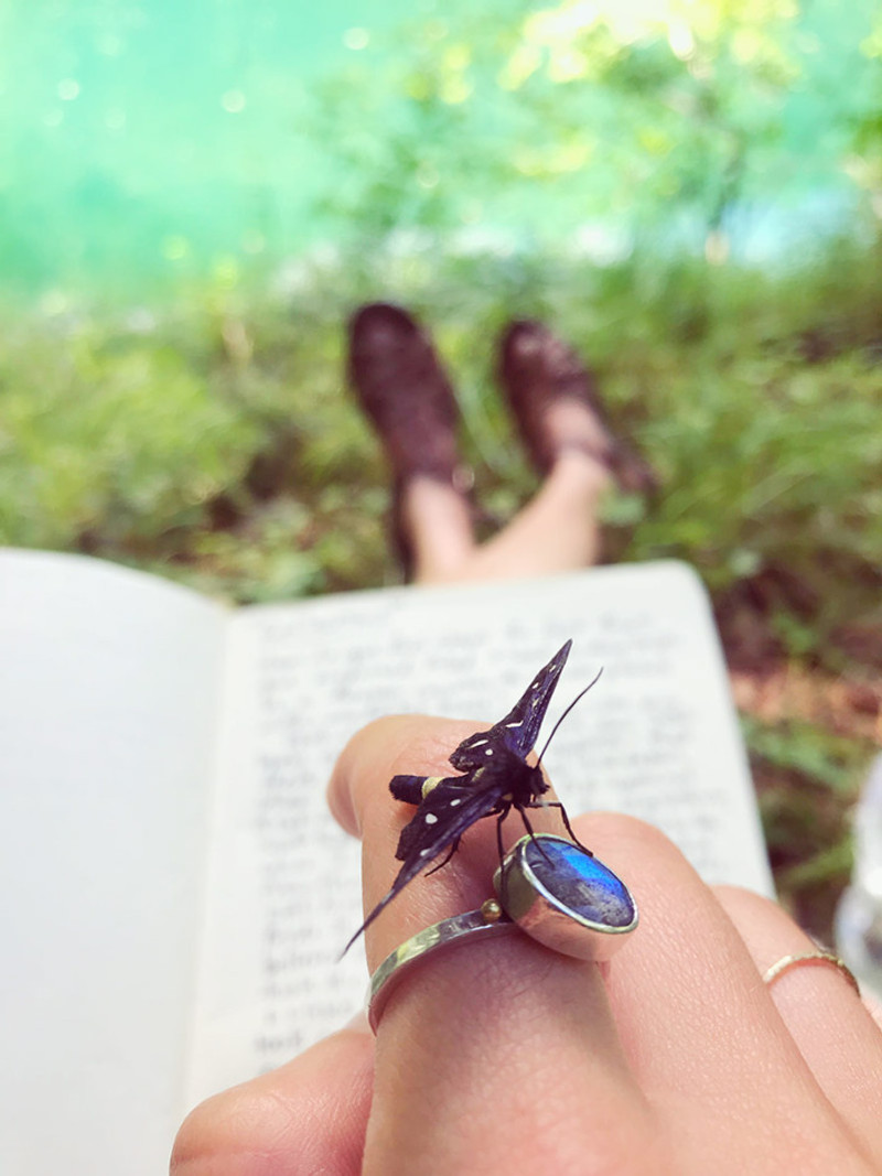butterfly resting on a blue ring on a hand with an open journal on her lap and teal water at her feet