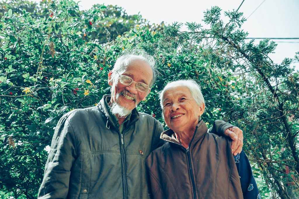 an older asian couple smiling with the man's arm around the woman