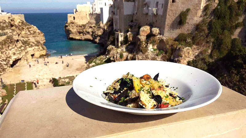 seafood dish with the village of polignano