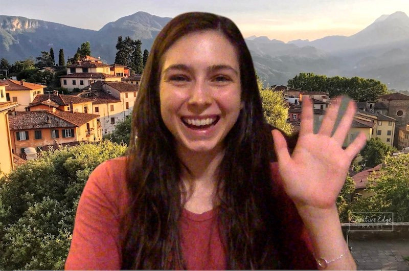 woman waving with a zoom background of an italian mountain village