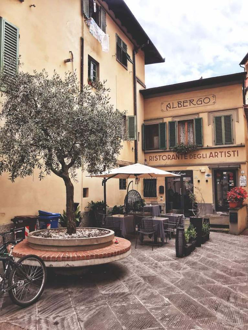 """secret scenic corner of a hidden town in Mugello, Tuscany. Courtyard with an olive tree and art nouveau font spelling """"Albergo"""" (hotel) on the building"""