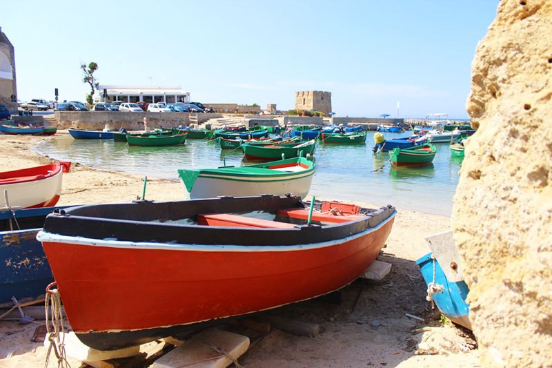 red boat in a small bay with fort in polignano a mare italy