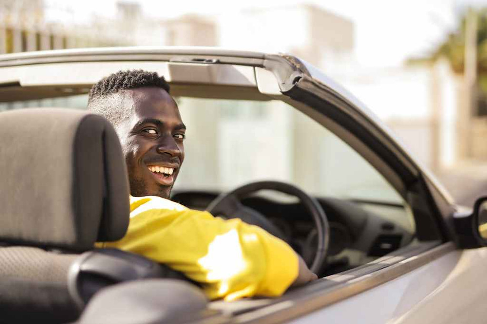 black guy in bright yellow shirt driving a convertible car