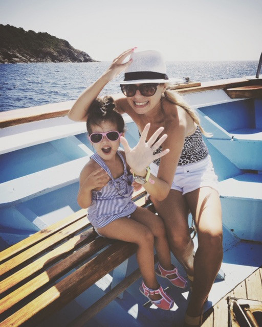 blonde italian woman holding onto her white hat and waving at the camera with her little girl on a boat