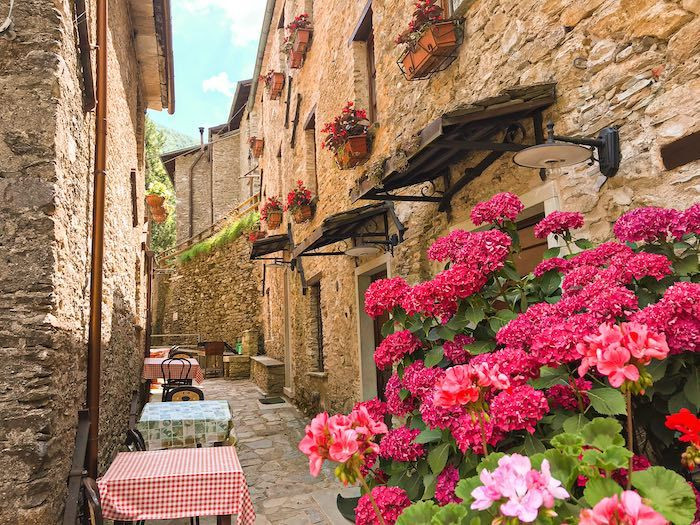 Charming alleyway in an Italian stone village with beautiful pink flowers under the windows and little tables for a restaurant