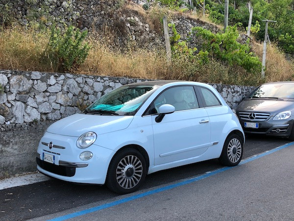 light blue Fiat car parallel parked in Italy
