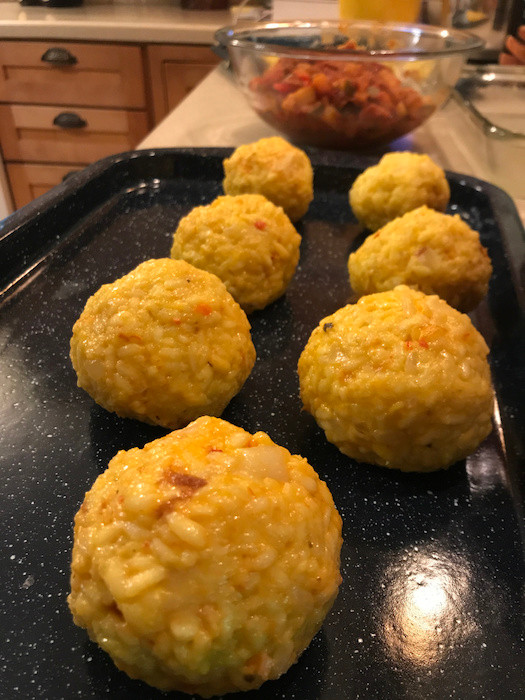 arancini on a tray before being breaded and fried