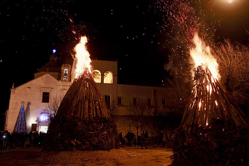 two huge bonfires at night with an old italian building in the back