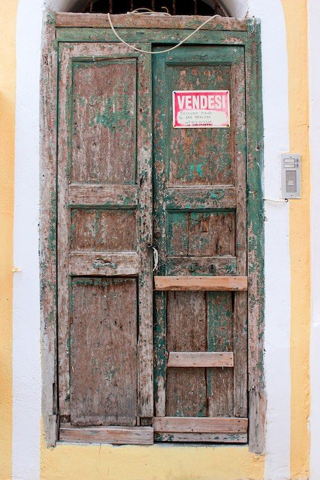 old weathered door with an Italian for sale sign on it