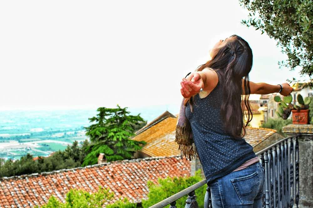 girl with open arms over beautiful rooftop view in italy