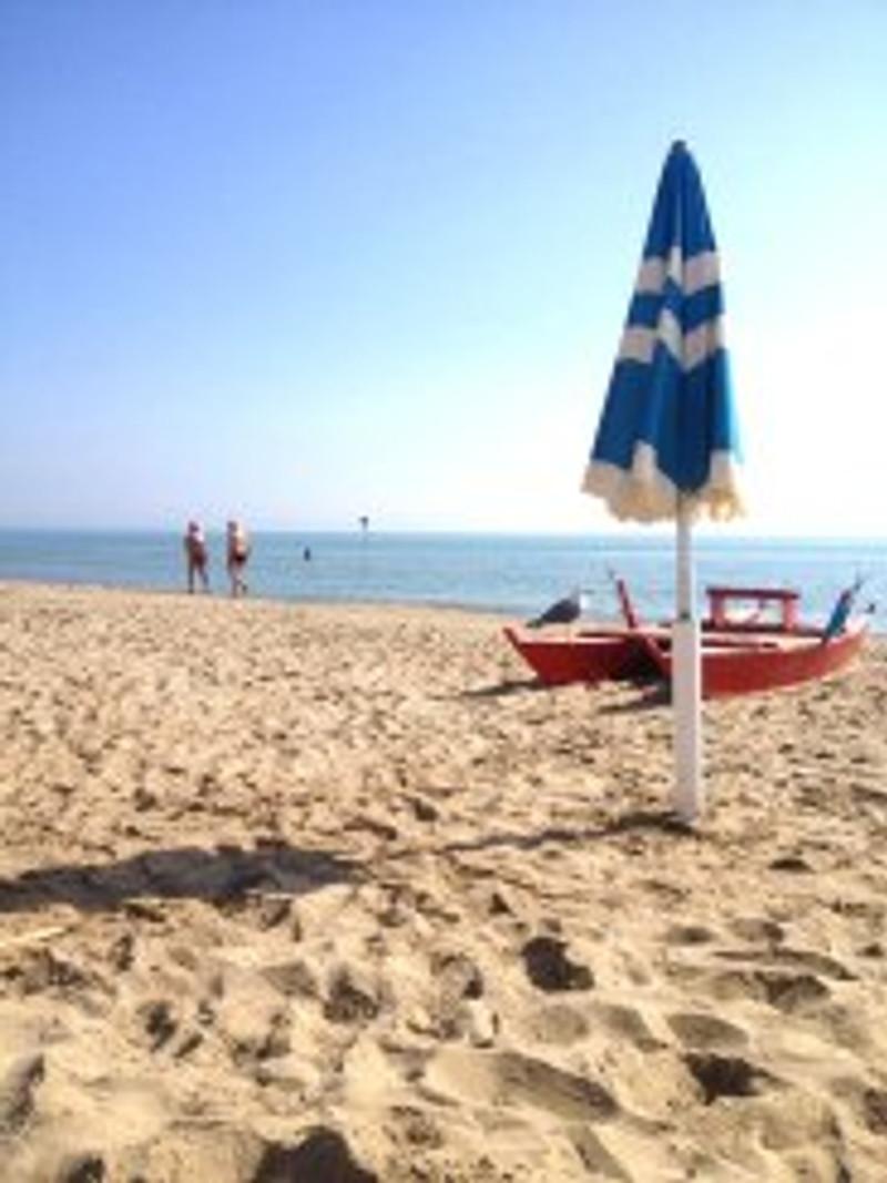golden beach blue umbrella red boat couple on seashore italy abruzzo