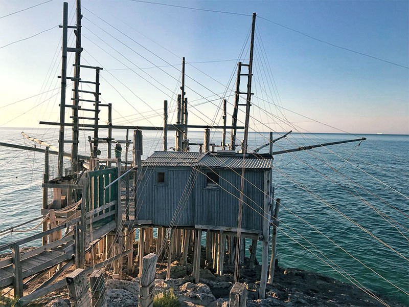 A metal house on wooden stilts at the oceans edge with wires and beams sticking out in all directions supporting fishing nets.