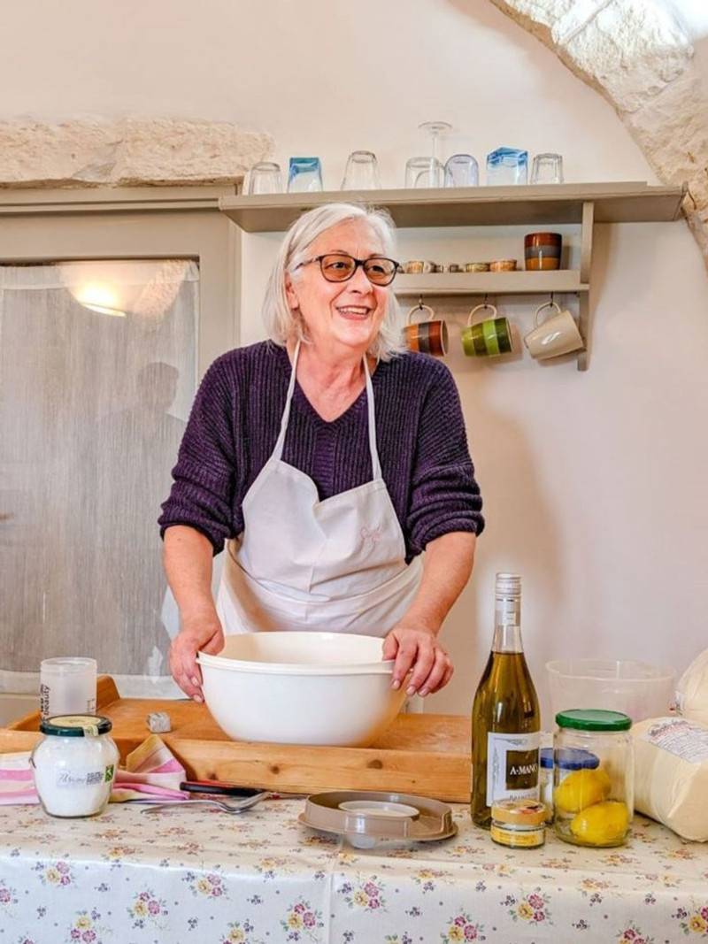 Smiling white haired Italian woman mid instruction, in a rustic kitchen.