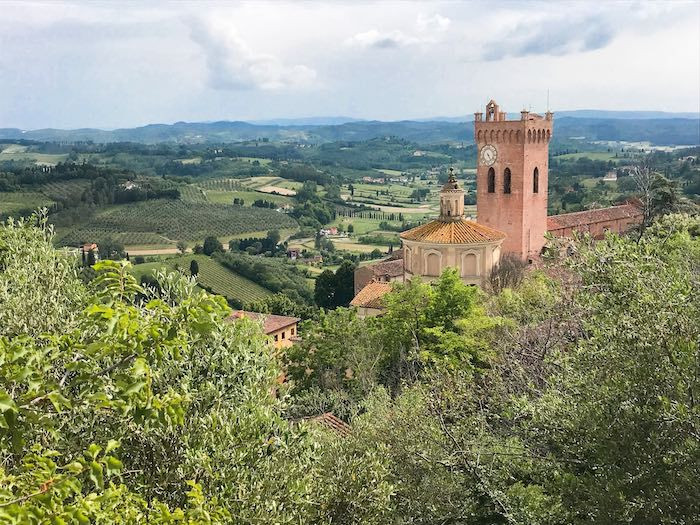 The majestic view from San Miniato in Tuscany, Italy with a clocktower, baptistry, and countryside