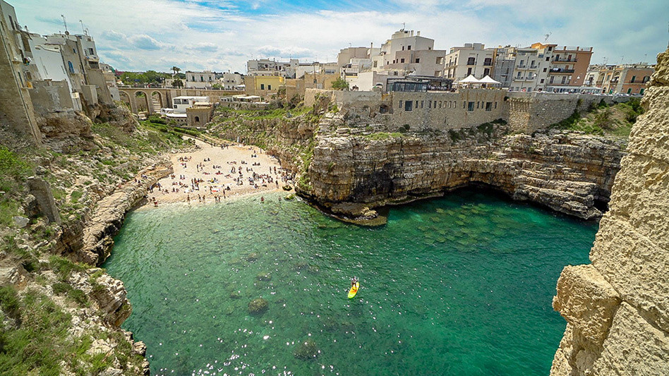 White Buildings on a cliff overlooking turquoise waters, sun bathers on a beach and a person on a yellow paddle board.