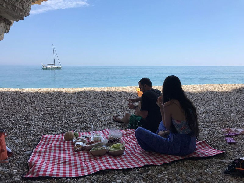 A man and a woman enjoying a picnic on a red checked blanket on an isolated pebble beach, looking out on blue water and a white sail boat.
