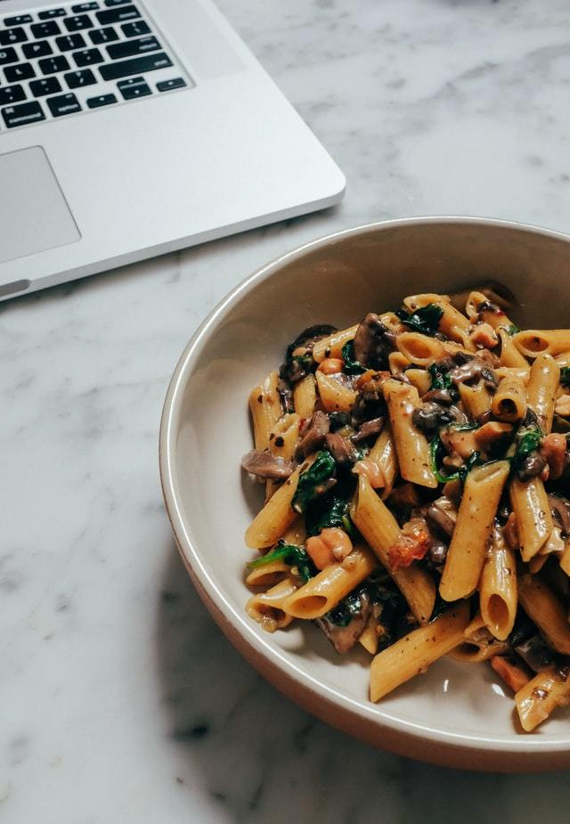 dish of penne pasta with sardines next to a laptop