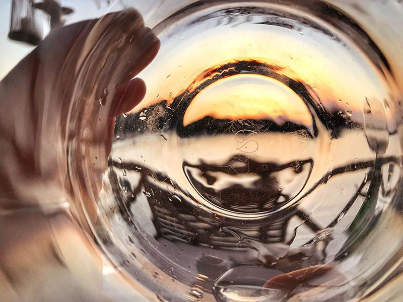 the sunset seen through an empty water glass