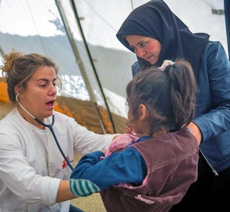 An MSF nurse attending a girl in Lesvos, Greece. ©Jodi Hilton