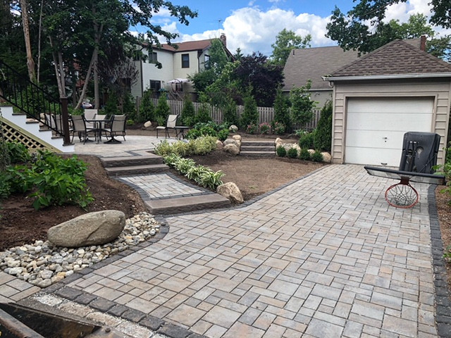 paver driveway that leads to stone, rock, pebble, shrub surrounding outdoor recreational area, stunning design of hardscape and softscape