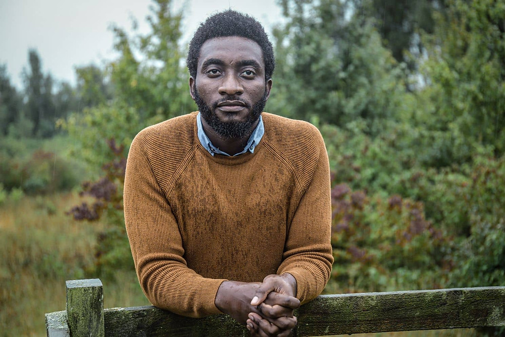 Tolulope Olajide rests hand a wooden gate, beaten by the rain and staring ahead